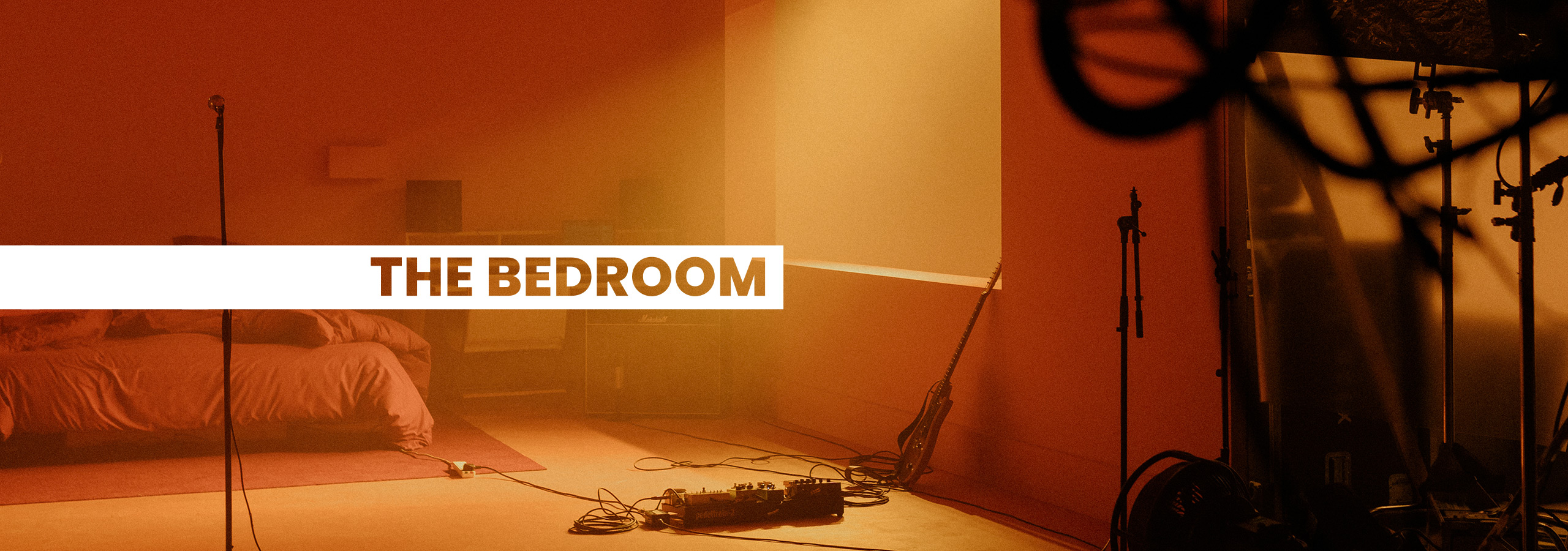 Image of a bedroom with music production gear in the corner